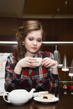 Молодые женщины в чае рубашки шотландки выпивая Стоковая Фотография RF
