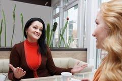 Молодые женщины говоря в малом кафе Стоковая Фотография