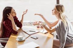 Молодые женщины говоря пока имеющ встречу бизнес-ланча в кафе Стоковая Фотография RF
