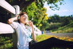 Молодые женщины лежа в траве лета с наушниками слушая к музыке стоковые изображения