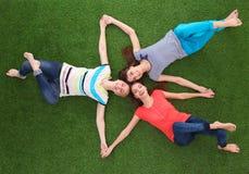 Молодые женщины лежа на зеленой траве Стоковая Фотография