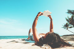 Молодые женщины лежа на тропическом пляже, ослабляют с книгой Стоковое Изображение