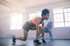 Молодые женщины делая разминку совместно в спортзале Стоковое Фото