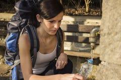 Молодые женщины заполняют бутылку Стоковое Фото