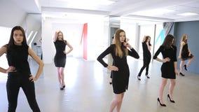 Молодые женщины изменяют представление стоя в образцово-показательной школе акции видеоматериалы