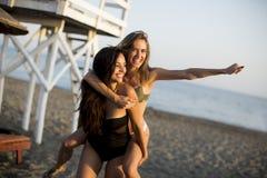 Молодые женщины имея потеху на пляже Стоковое фото RF