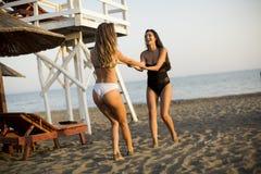 Молодые женщины имея потеху на пляже Стоковое Фото