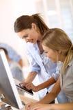 Молодые женщины используя таблетку на офисе Стоковая Фотография RF