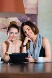 Молодые женщины или коллеги сидя в кафе или ресторане Стоковая Фотография