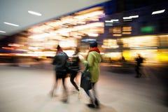 Молодые женщины идя вниз с торговой улицы на сумраке Стоковое Изображение