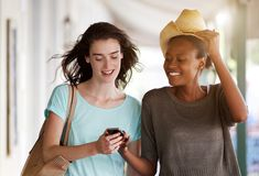 Молодые женщины идя совместно используя мобильный телефон Стоковое Изображение RF
