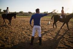 Молодые женщины мужского тренера направляя в верховой лошади Стоковое Изображение