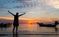 молодые женщины наслаждаясь естественным заходом солнца на пляже Стоковая Фотография RF
