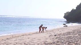 Молодые женщины находя раковины на пляже океан bali Индонесия акции видеоматериалы
