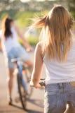 Молодые женщины на велосипедах, вид сзади Стоковое фото RF
