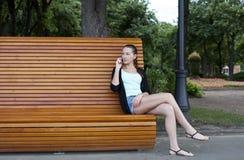 Молодые женщины на скамейке в парке лета Стоковые Фотографии RF