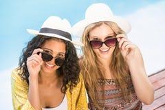 Молодые женщины нося солнечные очки имея потеху около бассейна Стоковая Фотография
