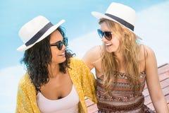 Молодые женщины нося солнечные очки имея потеху около бассейна Стоковое фото RF