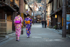 Молодые женщины нося традиционное японское кимоно идут на улицу Gion Стоковая Фотография RF