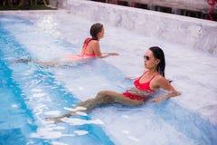 Молодые женщины ослабляя на бассейне Стоковая Фотография