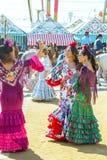 Молодые женщины одели в красочных платьях на ярмарке Севильи апреля в Испании стоковая фотография