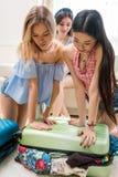 Молодые женщины пакуя чемодан на каникулы совместно дома Стоковое Изображение RF