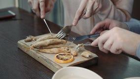 Молодые женщины пар и человек беседуя, имеющ пить в кафе кофейни города, беседу и едят рыб в бэттере видеоматериал