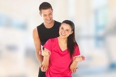 Женщина при ее личный тренер пригодности работая с весами в спортзале Стоковая Фотография RF