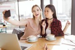 Молодые женщины принимая selfie пока выпивающ кофе внутри помещения на встрече на обеде Стоковая Фотография RF