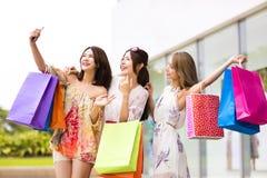 молодые женщины принимая Selfie пока ходящ по магазинам Стоковая Фотография