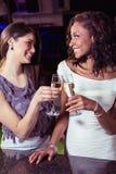 Молодые женщины провозглашать каннелюры шампанского на счетчике бара Стоковые Фотографии RF