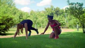 Молодые женщины работая в парке Разминка фитнеса внешняя акции видеоматериалы