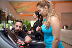 Молодые женщины разрабатывая в спортзале с тренером Стоковая Фотография RF