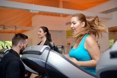 Молодые женщины разрабатывая в спортзале с тренером Стоковые Фотографии RF