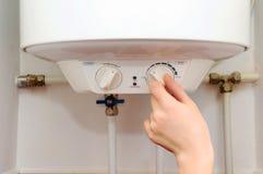Молодые женщины рук установили температуру воды в электрическом котле Закройте вверх женских рук поворачивая ручку избирать Стоковые Фотографии RF