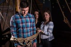 Молодые женщины связывают молодого унылого парня к столбцу на палубе shi Стоковое Изображение RF