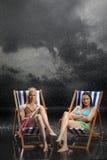 Молодые женщины сидя в Sunloungers в дожде Стоковое Изображение RF