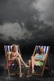 Молодые женщины сидя в Sunloungers в дожде Стоковая Фотография RF