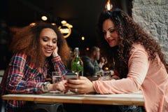 Молодые женщины сидя на кафе используя мобильный телефон Стоковая Фотография