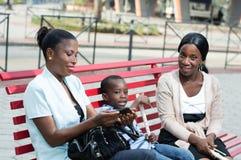 Молодые женщины сидя на стенде с ребенком Стоковые Изображения RF