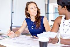 Молодые женщины сидя на столе в офисе и работая на светокопии Стоковая Фотография
