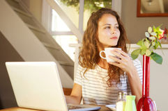 Молодые женщины сидя на таблице с компьтер-книжкой и кофе Стоковые Фотографии RF