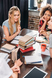 Молодые женщины сидя совместно на таблице и изучая с книгами и тетрадями Стоковое фото RF