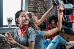 Молодые женщины сидя спина к спине пока пишущ в тетради и использующ цифровую таблетку Стоковые Фотографии RF