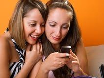 Молодые женщины смотря мобильный телефон Стоковое фото RF