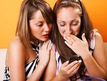 Молодые женщины смотря мобильный телефон Стоковые Изображения