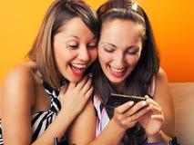 Молодые женщины смотря мобильный телефон Стоковые Фотографии RF