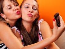 Молодые женщины смотря мобильный телефон Стоковая Фотография