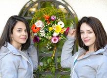 Молодые женщины смотря на один другого с цветками между ими Стоковая Фотография