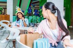 Молодые женщины смотря один другого пока сидящ в торговом центре Стоковое Изображение